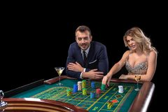 Couple gambling at roulette table in casino stock photos