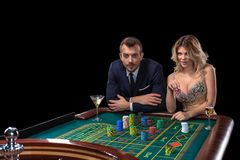 Couple gambling at roulette table in casino stock images