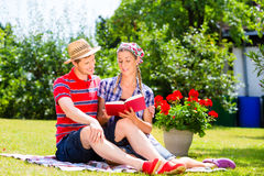 Couple in garden on blanket reading book Stock Photography