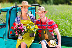 Couple in garden with flowers on gape. Happy couple in garden with flowers on gape Stock Photo