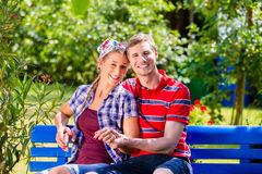 Couple in garden sitting on bench Royalty Free Stock Photos