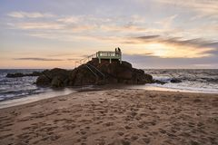 Couple on the gazebo over the rocks in the ocean stock images