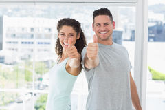 Couple gesturing thumbs up in bright exercise room Stock Photo