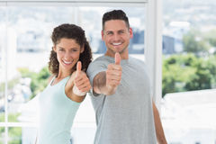 Couple gesturing thumbs up in exercise room Stock Image