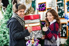 Couple Gesturing Thumbs Up While Holding Christmas. Portrait of young couple gesturing thumbs up while holding stacked Christmas presents at store Stock Photos