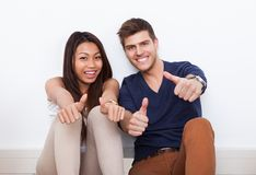 Couple gesturing thumbs up at home. Portrait of happy young multiethnic couple gesturing thumbs up at home Royalty Free Stock Photography
