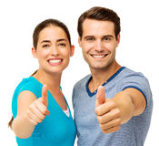 Couple Gesturing Thumbs Up Over White Background. Portrait of happy young couple gesturing thumbs up over white background. Horizontal shot Royalty Free Stock Image