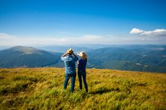 Travel to unknown places. The couple get lost in the mountains, engaged in navigation by using phone and binoculars Stock Images