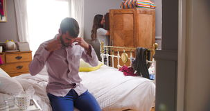 Couple Getting Dressed For Work In Bedroom. Man sitting on bed getting dressed for work as woman chooses clothes from wardrobe.Shot on Sony FS700 at frame rate stock video footage