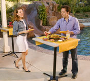 Couple getting food at poolside. Caucasion couple at the side of the pool getting mexican food appetizers in a party setting Stock Photos