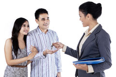 Couple getting keys of their new home. Happy couple getting keys of their new home from businesswoman Stock Images