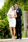 Couple Getting Married. An attractive young bride and groom standing on steps outdoors Stock Image