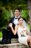 Couple Getting Married. An attractive young bride and groom sitting on steps and holding hands outdoors Royalty Free Stock Photo