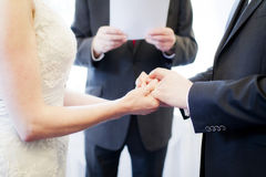 Couple getting married. Hands of young couple getting married with priest or vicar in background Royalty Free Stock Photo