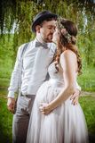 Couple getting married outside. Photo of a pregnant bride and groom kissing during the wedding ceremony Royalty Free Stock Photography