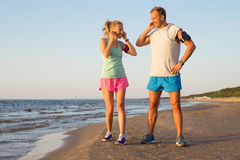 Couple getting ready for their run along the beach Royalty Free Stock Images