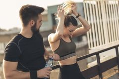Couple getting ready for workout. Young couple standing on a building rooftop terrace, getting ready for a workout royalty free stock images
