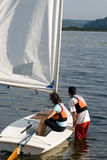 Couple Getting into Sailboat on Water - Vertical Royalty Free Stock Images