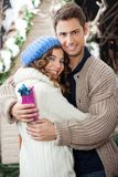 Couple With Gift Box Embracing At Christmas Store Royalty Free Stock Images