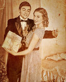 Couple with gift box. Sepia toned. Couple on party drinking champagne .Sepia toned Stock Images