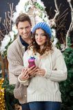 Couple With Gift Box Standing At Christmas Store Royalty Free Stock Images
