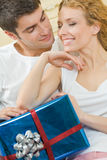 Couple with gift at home Stock Photography