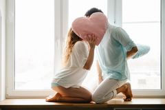 Free Couple Girl And Guy Play With Pillows Near Window. Royalty Free Stock Photos - 138652538
