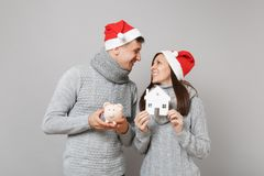 Couple girl guy in red Santa Christmas hat sweaters scarves hold pig house isolated on grey wall background studio