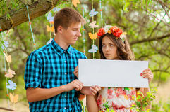 Couple girl and man with white sign in his hands Royalty Free Stock Photography