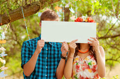 Couple girl and man with white sign in his hands Stock Photos