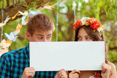 Couple girl and man with white sign in his hands Royalty Free Stock Image