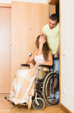 Couple with girl in wheelchair near door Royalty Free Stock Images