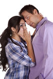 Couple girl whispering. A man and woman up close.  She is whispering to him Stock Photos