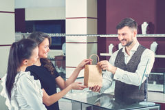 Couple of girlfriend buying present in jewelry store. Two pretty women buying jewelry in mall. Jeweler seller and two girls holding little paper bag by arms Royalty Free Stock Photos