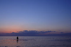 A couple of girls in dresses standing in the sea at sunset Stock Images