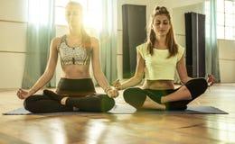 Couple of girls making yoga Stock Photos
