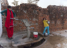 Couple girls pumping water from communal pump. Stock Photography