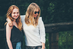 Couple girls walking together hugging Royalty Free Stock Images