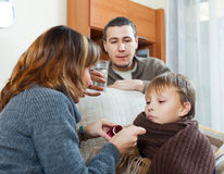 Couple giving cough syrup to unwell boy Stock Image