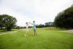 Couple giving high five to each other. In golf course Royalty Free Stock Photography