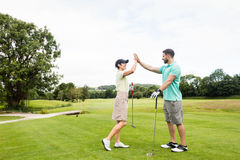 Couple giving high five to each other. In golf course Stock Photography