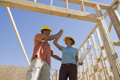 Couple Giving Highfive To Each Other. Low angle view of an African American couple at construction site giving high-five Stock Images