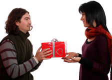 Couple giving a present. Young man giving a present to a pretty woman Royalty Free Stock Images
