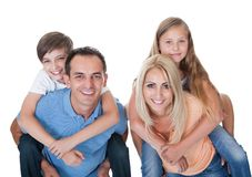 Couple Giving Two Young Children Piggyback Rides royalty free stock photos
