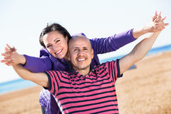 Couple gladly hugging each other and enjoying the beach Royalty Free Stock Photos