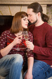Couple with glass of champagne embracing together near fireplace Stock Photo