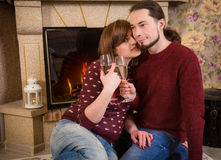 Couple with glass of champagne together near fireplace Royalty Free Stock Images