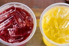 A couple of glass, red and yellow color, is on the wooden table. With ice ready to drink for refreshment royalty free stock image