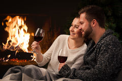 Couple with glass of wine at fireplace Stock Images