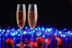 A couple of glasses with champagne on a black glossy table with. Christmas balls and red ribbon  on the dark background  with blue bokeh. Happy new year concept Stock Images